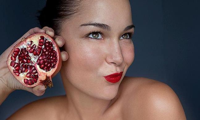 Woman holding halved pomegranate